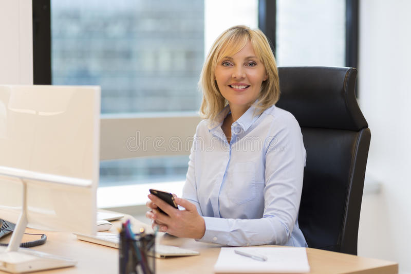 Porträt einer Mitte alterte die Geschäftsfrau, die im Büro arbeitet stockfotos