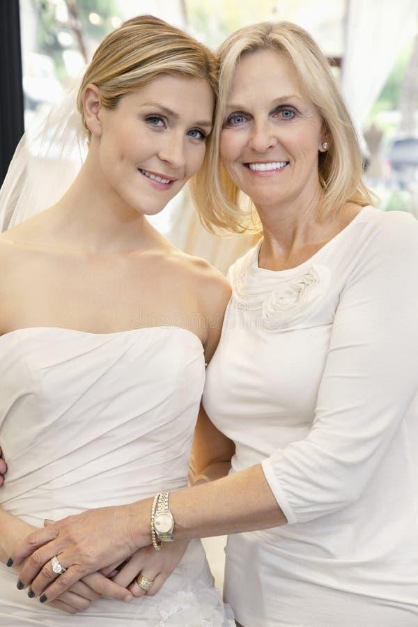 Porträt einer Mutter mit der Tochter gekleidet als Braut im Brautspeicher lizenzfreie stockfotografie
