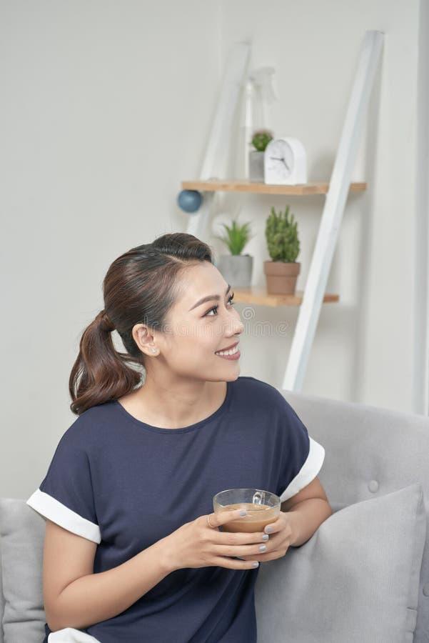 Porträt einer nachdenklichen Frau, die einen entspannenden Tasse Kaffee hält, sitzen lizenzfreie stockbilder