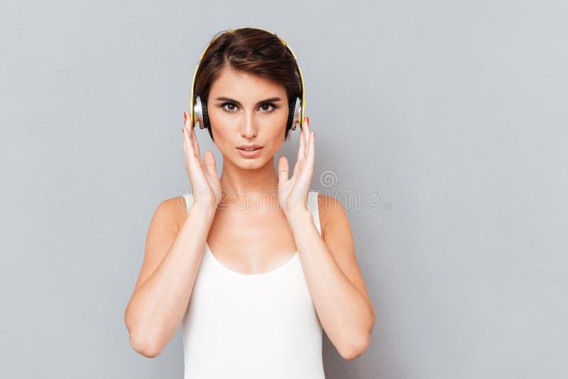 Porträt einer nachdenklichen starken hörenden Musik der Frau in den Kopfhörern stockfotografie