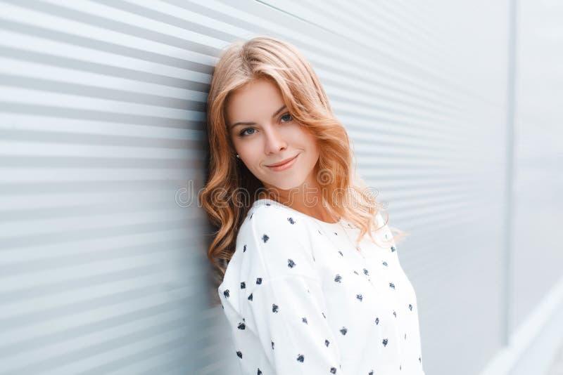 Porträt einer netten attraktiven jungen Frau mit einem schönen Lächeln mit blauen Augen in der stilvollen Frühlingskleidung nahe  lizenzfreies stockbild