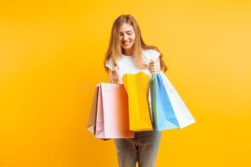 Porträt einer neugierigen jungen Frau, nach einem guten Einkaufen, schauend innerhalb der Tasche, lokalisiert auf einem gelben Hi lizenzfreies stockbild