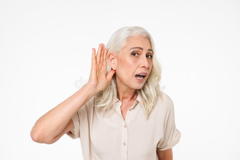 Porträt einer neugierigen reifen Frau, die versucht, etwas zu hören stockbild