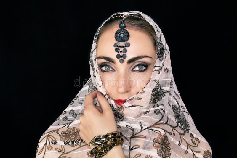 Porträt einer orientalischen jungen Frau in einem Schal mit einer Verzierung und Juwelen auf einem schwarzen Hintergrund stockbild