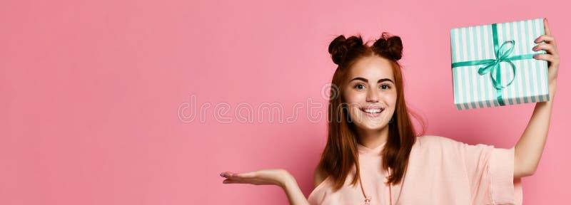 Porträt einer recht lächelnden Rothaarigemädchenholdinggeschenkbox und -c$betrachtens sie, lokalisiert über Farbrosa Hintergrund lizenzfreie stockbilder