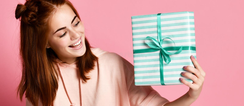 Porträt einer recht lächelnden Rothaarigemädchenholdinggeschenkbox und -c$betrachtens sie, lokalisiert über Farbrosa Hintergrund lizenzfreie stockfotos
