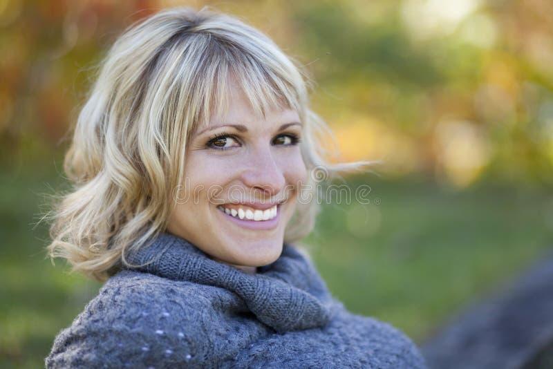 Porträt einer reifen Frau, die am Park lächelt lizenzfreie stockbilder