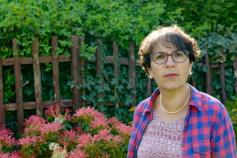Porträt einer reifen Frau im Garten lizenzfreie stockfotos