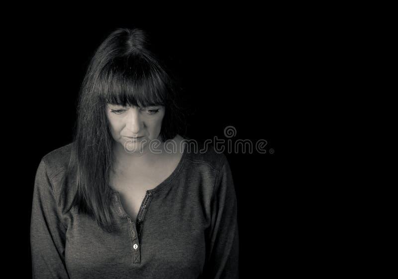 Porträt einer reifen gestörten Frau, die unten schaut stockbild