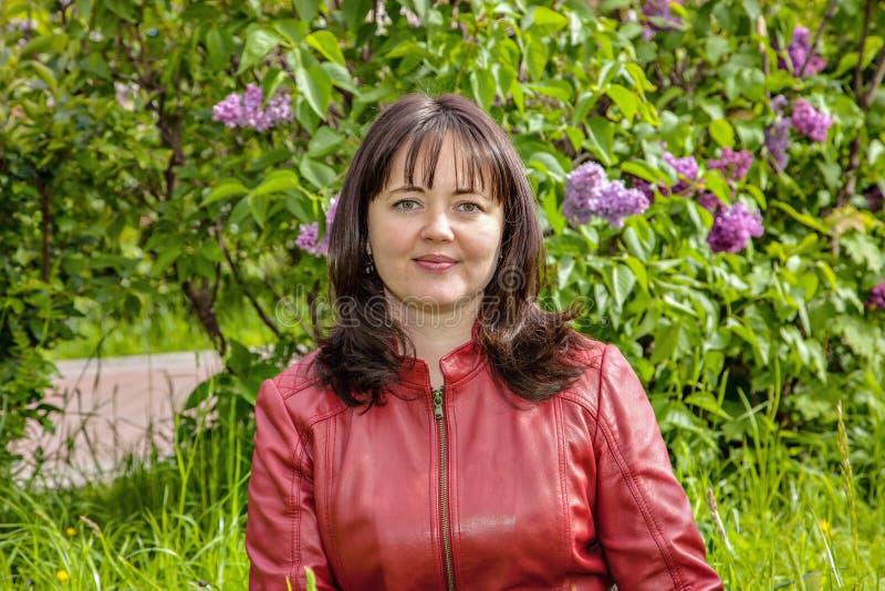 Porträt einer ruhigen Schönheit unter den Blüten einer blühenden Flieder für einen Weg im Park lizenzfreies stockfoto