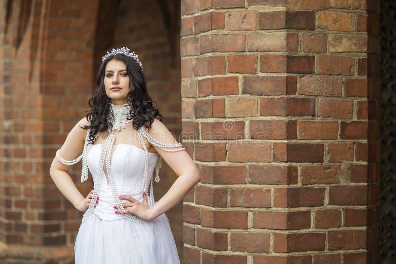 Porträt einer ruhigen, sensual-kaukasischen Braut mit Kronen- und Fußketten-Posen gegen alte Mauern Außendoos stockfotos