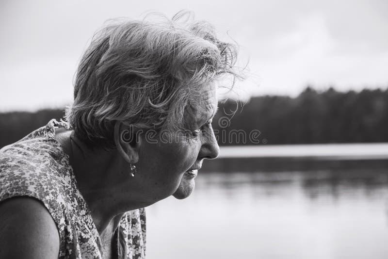 Porträt einer schönen älteren Frau, die den Fluss betrachtet stockfotografie