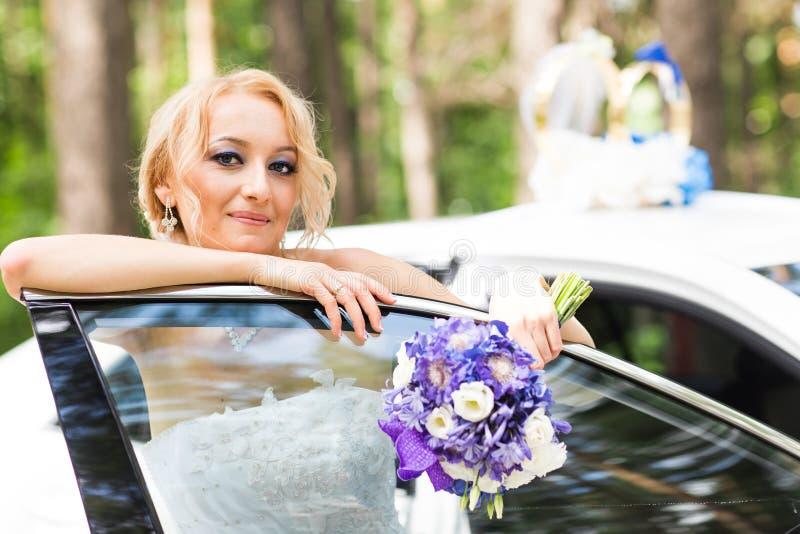 Porträt einer schönen blonden Braut mit dem Hochzeitsauto lizenzfreie stockfotografie