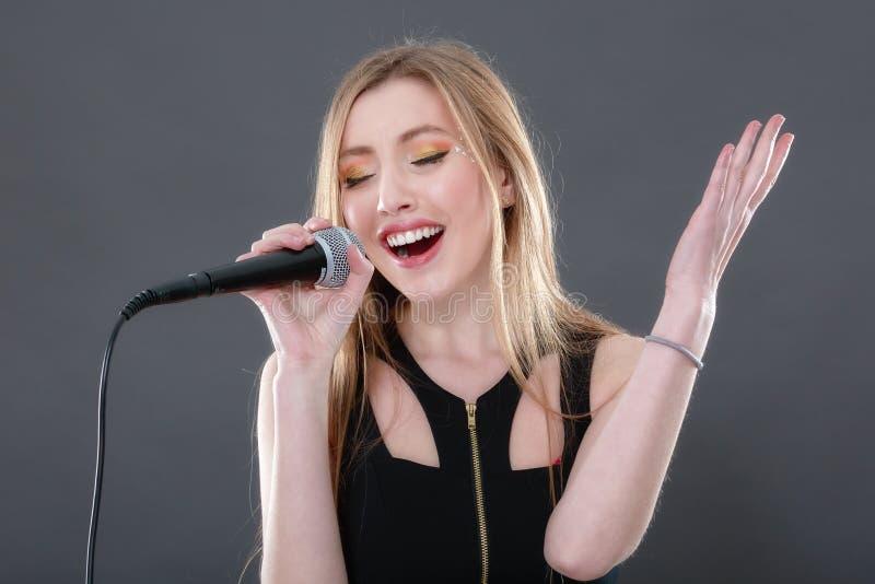 Porträt einer schönen blonden jungen Frau, die in micropho singt stockfotos