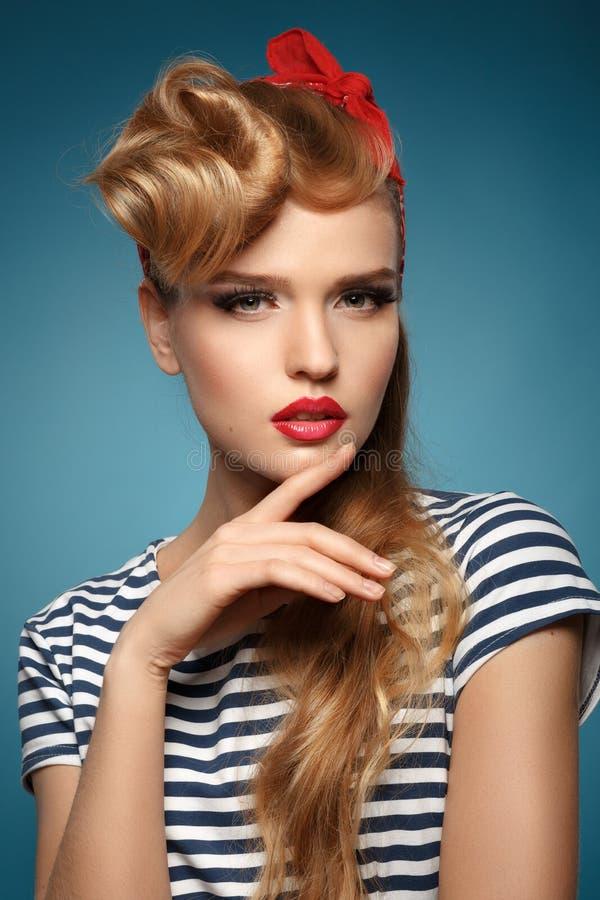 Porträt einer schönen Blondine mit rotem Schal auf dem Kopf lizenzfreie stockbilder