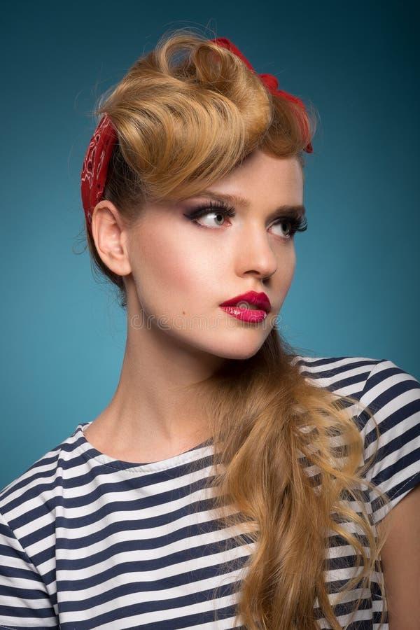 Porträt einer schönen Blondine mit rotem Schal auf dem Kopf stockbild