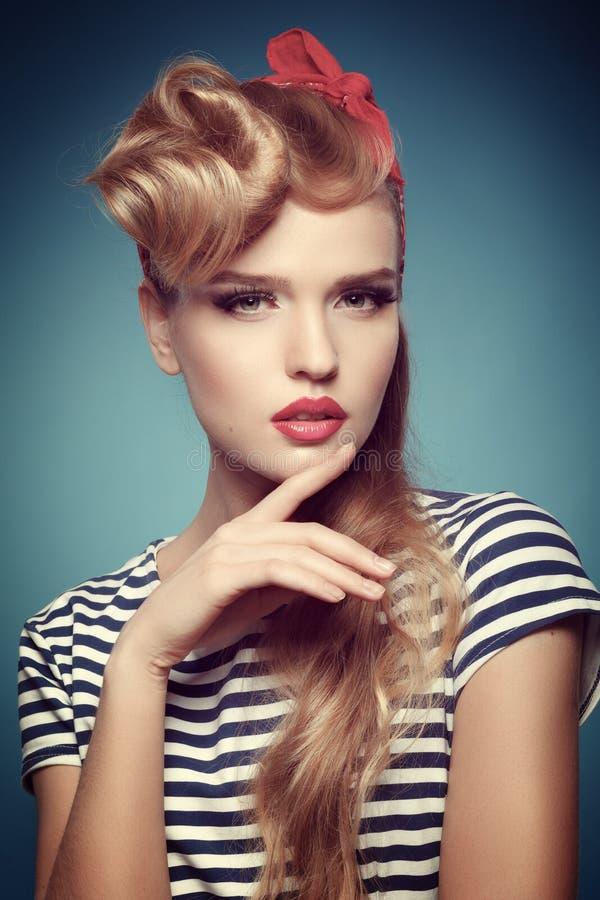 Porträt einer schönen Blondine mit rotem Schal auf dem Kopf lizenzfreie stockfotografie