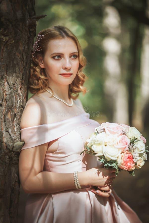 Porträt einer schönen Braut, die nahe einem Baum steht stockfotografie