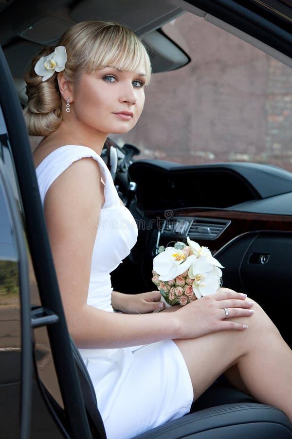Porträt einer schönen Braut in einem Auto mit einem Blumenstrauß von Blumen stockbilder