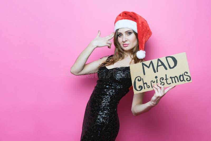 Portr?t einer sch?nen brunette Frau in der Weihnachtshutholding und im vorz?glichen schwarzen Kleid ein Zeichen ?w?tendes Weihnac lizenzfreie stockfotos