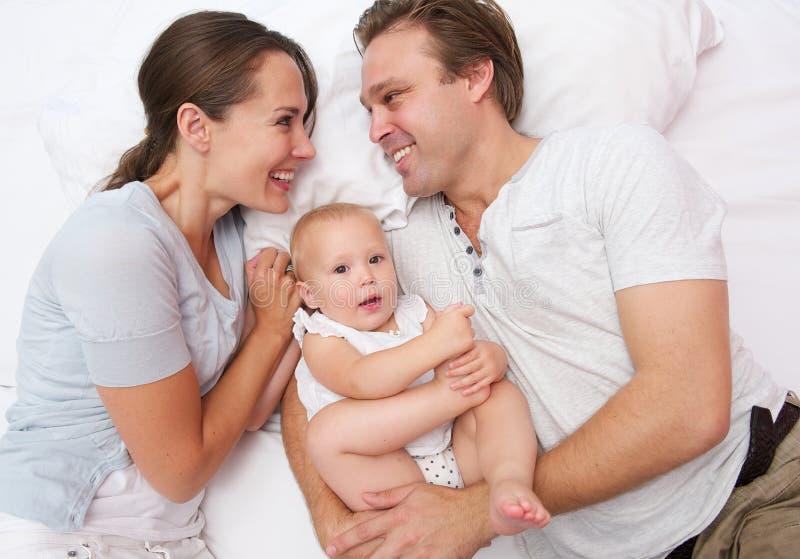 Porträt einer schönen Familie, die im Bett mit nettem Baby liegt stockfotos