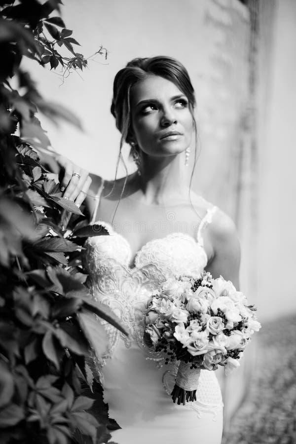 Porträt einer schönen glücklichen Brunettebraut in heiratendem weißem Kleiderhändchenhalten im Blumenstrauß von Blumen draußen stockfotografie