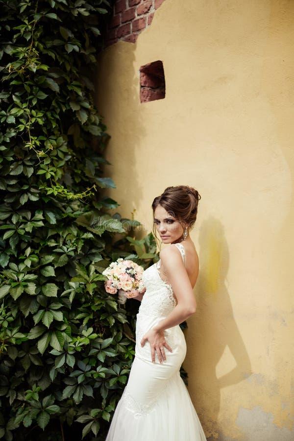 Porträt einer schönen glücklichen Brunettebraut in heiratendem weißem Kleiderhändchenhalten im Blumenstrauß von Blumen draußen lizenzfreies stockbild