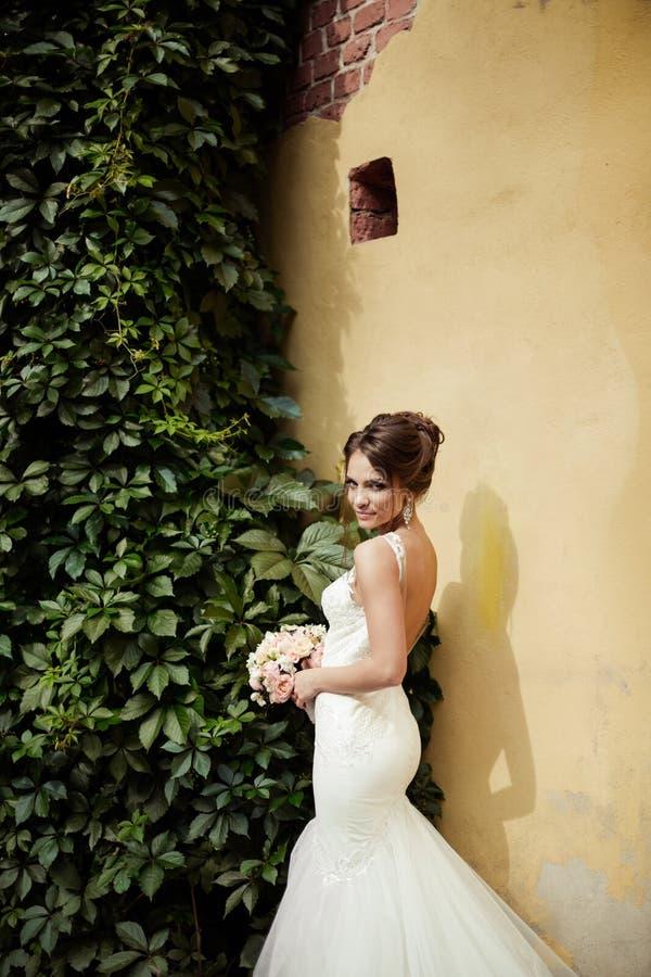 Porträt einer schönen glücklichen Brunettebraut in heiratendem weißem Kleiderhändchenhalten im Blumenstrauß von Blumen draußen stockfoto