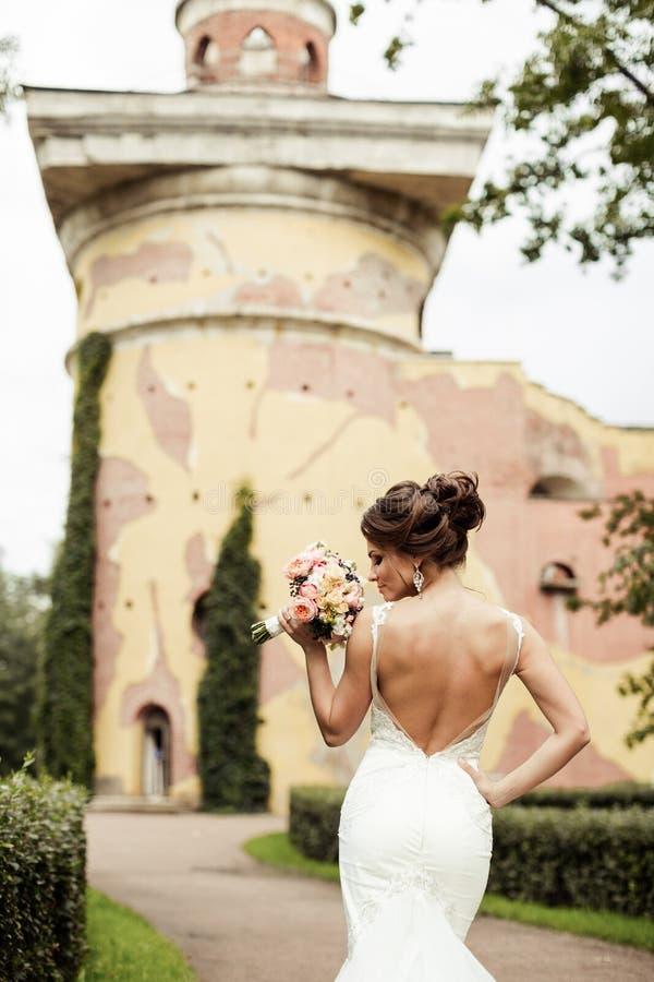 Porträt einer schönen glücklichen Brunettebraut in heiratendem weißem Kleiderhändchenhalten im Blumenstrauß von Blumen draußen lizenzfreies stockfoto
