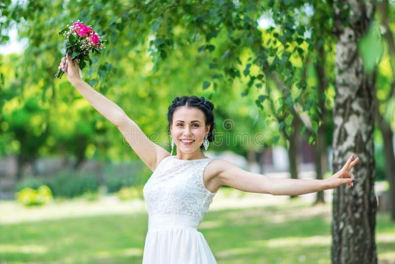 Porträt einer schönen glücklichen jungen weiblichen Braut mit dem lächelnden Anheben des kleinen Hochzeitsrosablumenrosen-Blumens stockbild