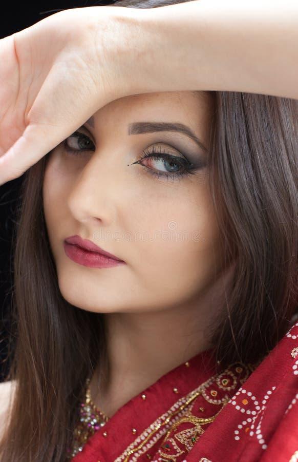 Porträt einer schönen indischen Frau, die einen roten Sari trägt stockbild