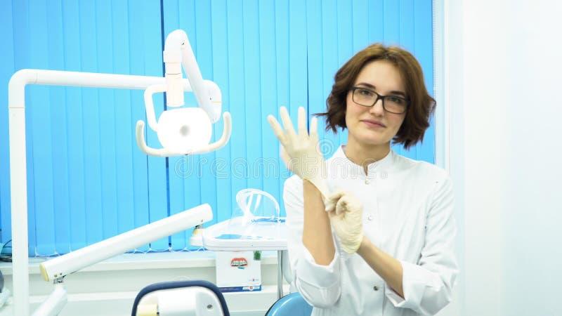 Porträt einer schönen, jungen Ärztin, die medizinische Handschuhe trägt Weiblicher Zahnarzthelfer in den Gläsern, die auf Handsch stockfotografie