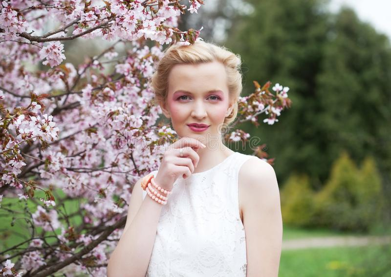 Porträt einer schönen jungen blonden Frau auf einem Hintergrund von rosa Kirschblüten im Frühjahr stockfotografie