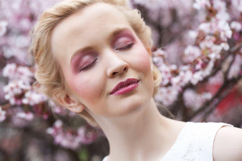 Porträt einer schönen jungen blonden Frau auf einem Hintergrund von rosa Kirschblüten im Frühjahr lizenzfreies stockfoto
