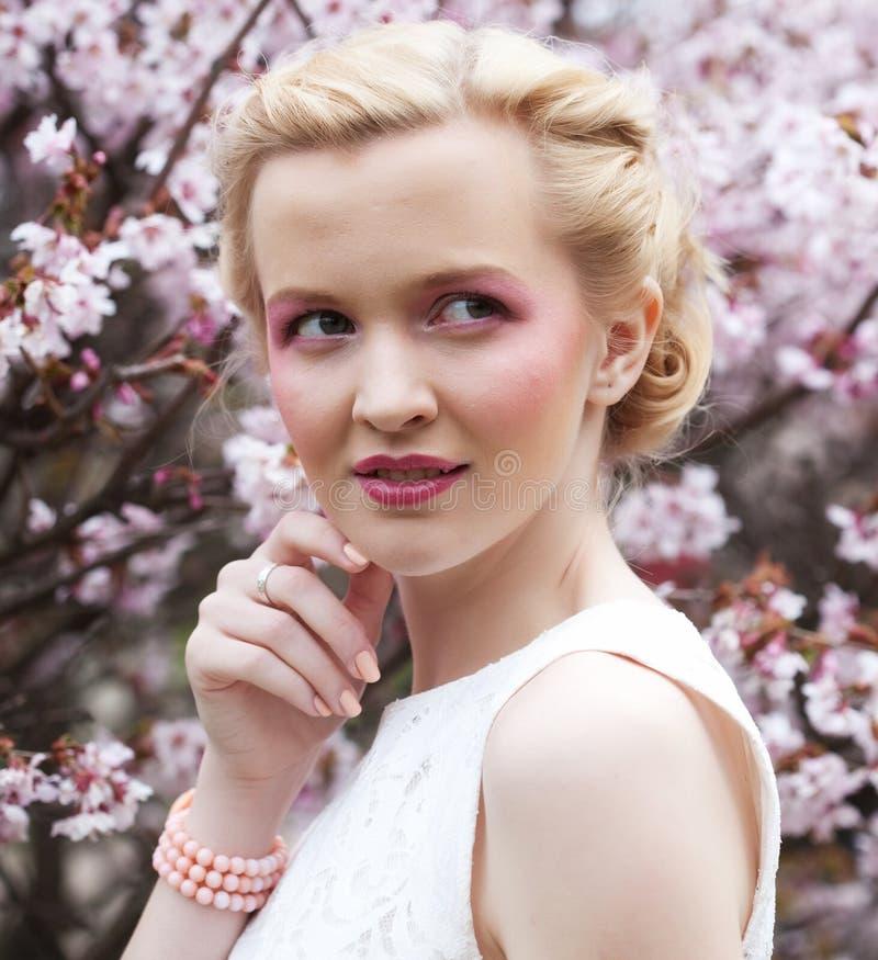 Porträt einer schönen jungen blonden Frau auf einem Hintergrund von rosa Kirschblüten im Frühjahr lizenzfreies stockbild