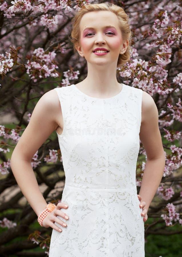 Porträt einer schönen jungen blonden Frau auf einem Hintergrund von rosa Kirschblüten im Frühjahr lizenzfreie stockbilder