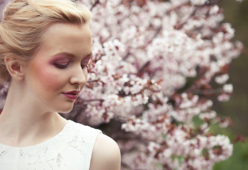 Porträt einer schönen jungen blonden Frau auf einem Hintergrund von rosa Kirschblüten im Frühjahr stockbilder