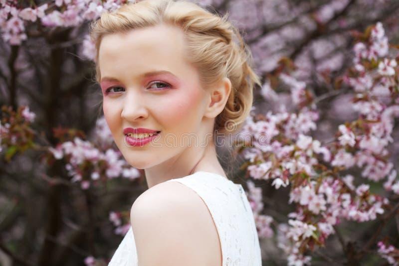 Porträt einer schönen jungen blonden Frau auf einem Hintergrund von rosa Kirschblüten im Frühjahr lizenzfreie stockfotos