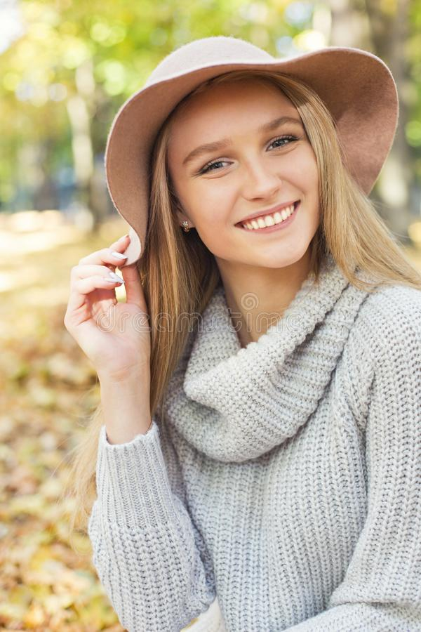 Porträt einer schönen jungen blonden Frau mit dem glänzenden geraden Haar in einem braunen Hut im Park stockfoto