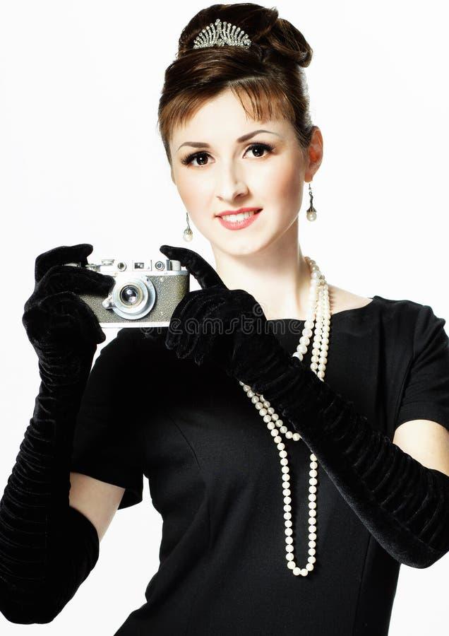 Porträt einer schönen jungen eleganten Frau mit einem Weinlese camer stockfoto