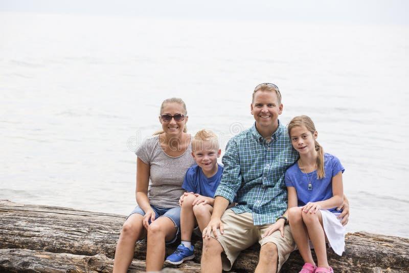 Porträt einer schönen jungen Familie am Rand eines Sees lizenzfreie stockbilder