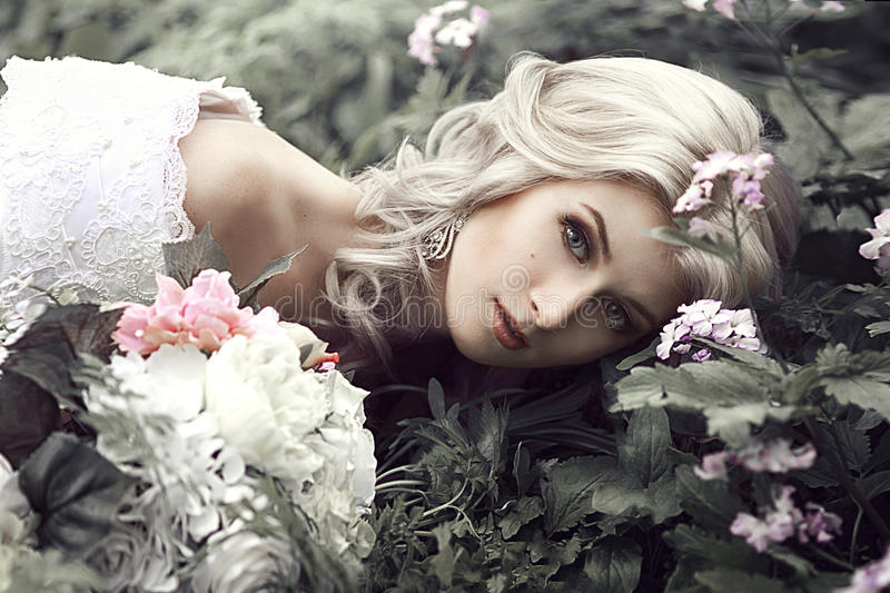 Porträt einer schönen jungen Frau als Prinzessin liegt in einem Wald mit Blumen stockfotos