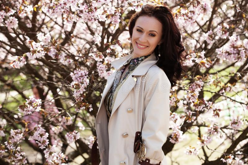 Porträt einer schönen jungen Frau auf einem Hintergrund von rosa Kirschblüten im Frühjahr lizenzfreies stockbild