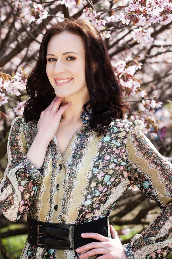 Porträt einer schönen jungen Frau auf einem Hintergrund von rosa Kirschblüten im Frühjahr stockfotos