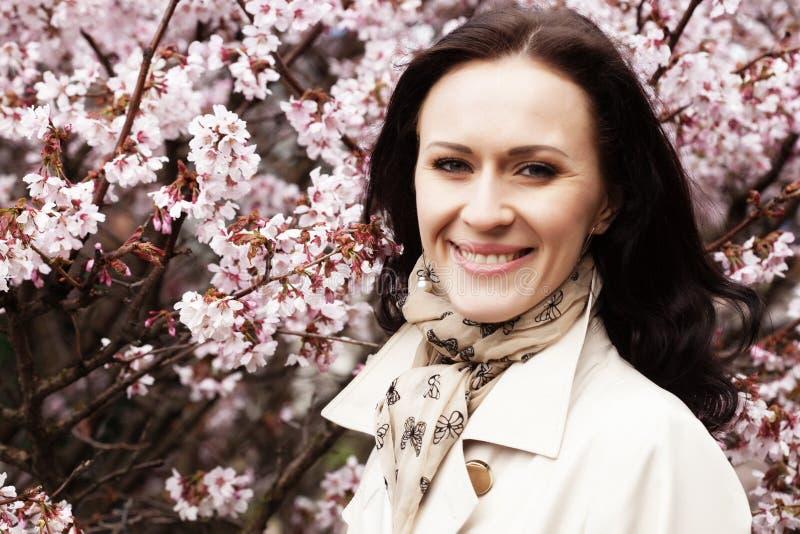 Porträt einer schönen jungen Frau auf einem Hintergrund von rosa Kirschblüten im Frühjahr, stockfotos
