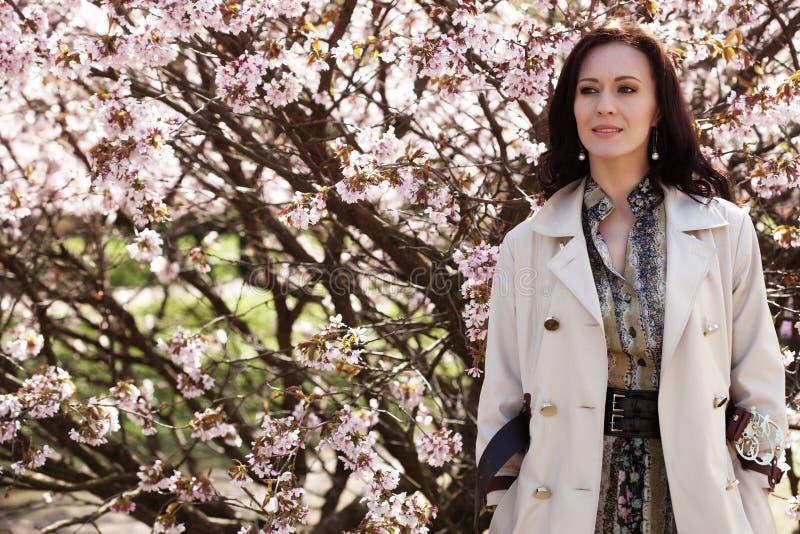 Porträt einer schönen jungen Frau auf einem Hintergrund von rosa Kirschblüten im Frühjahr, Lebensstilkonzept stockbilder