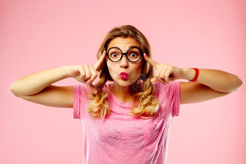 Porträt einer schönen jungen Frau in den lustigen Gläsern über rosa b stockfotografie
