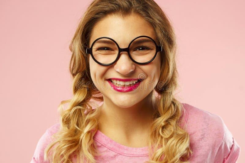Porträt einer schönen jungen Frau in den lustigen Gläsern über rosa b lizenzfreie stockfotos