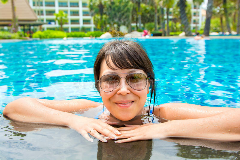 Porträt einer schönen jungen Frau in der Sonnenbrille im Pool stockbild
