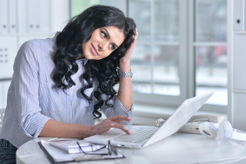 Porträt einer schönen jungen Frau, die im modernen Büro arbeitet lizenzfreies stockfoto